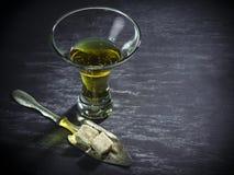 Exponeringsglas av absint med den sockerkuber och skeden Arkivfoton