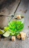 Exponeringsglas av absint med limefrukt- och sockerkuber Royaltyfria Foton