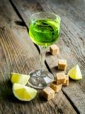 Exponeringsglas av absint med limefrukt- och sockerkuber Royaltyfri Foto