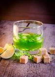Exponeringsglas av absint med limefrukt- och sockerkuber Arkivfoto