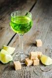 Exponeringsglas av absint med limefrukt- och sockerkuber Fotografering för Bildbyråer