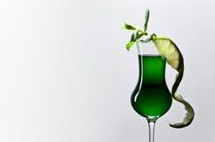 Exponeringsglas av absint som garneras med limefrukt och mintkaramellen Arkivbilder