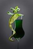 Exponeringsglas av absint som garneras med limefrukt- och mintkaramellsidor Arkivfoto