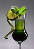 Exponeringsglas av absint som garneras med limefrukt- och mintkaramellsidor Royaltyfria Bilder