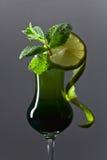 Exponeringsglas av absint som garneras med limefrukt- och mintkaramellsidor Fotografering för Bildbyråer