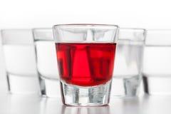 Exponeringsglas av alkohol Ett rött smaksatt, andra gör ren vodka royaltyfri bild