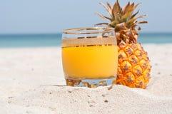 Exponeringsglas av ananasfruktsaft på en strand Arkivbilder