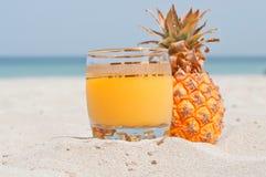 Exponeringsglas av ananasfruktsaft på en strand Royaltyfri Foto