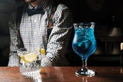 Exponeringsglas av blå vodka för coctailar på stångbakgrund royaltyfria bilder