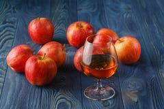 Exponeringsglas av Calvados konjak och röda äpplen Arkivfoton