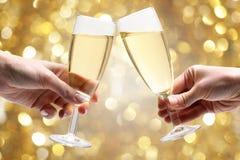 Exponeringsglas av champagne i händerna Royaltyfri Fotografi