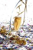 Exponeringsglas av champagne med banderoller och konfettiar Arkivfoto