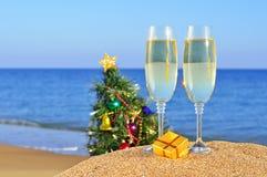 Exponeringsglas av champagne och julgranen på en strand Royaltyfri Fotografi