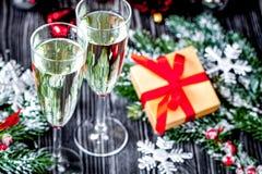 Exponeringsglas av champagne och julprydnader på mörk träbaksida Arkivbilder