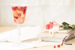 Exponeringsglas av champagne- och tranbärcoctailen med tappningböcker och Arkivfoto