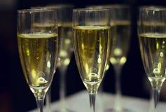 Exponeringsglas av champagne på en tabell arkivbilder