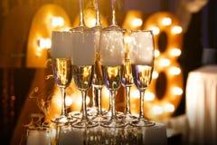 Exponeringsglas av champagne som göras i en pyramid för händelseparti- eller bröllopceremoni Royaltyfri Bild