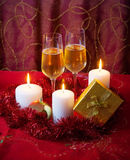Exponeringsglas av champagne, stearinljus, guld- gåvaask och rött glitter Arkivbilder