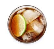 Exponeringsglas av coctailen med cola, is och klippt limefrukt på den vita bästa sikten royaltyfri foto
