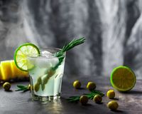 Exponeringsglas av coctailen på tabellen Oliv, rosmarin och limefrukt i ett G Royaltyfri Foto