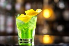 Exponeringsglas av coctailgräsplanfen med citronen och absint på stången kontrar Arkivfoto