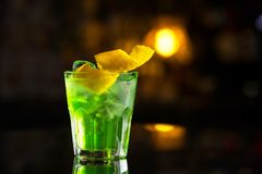 Exponeringsglas av coctailgräsplanfen med citronen och absint på stångstaen Arkivfoto