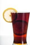 Exponeringsglas av cola med den skivade citronen arkivbilder