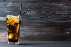Exponeringsglas av cola med is och limefrukt royaltyfria bilder