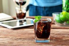 Exponeringsglas av cola med is och mintkaramellen Arkivfoton