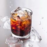 Exponeringsglas av cola och is Arkivbild