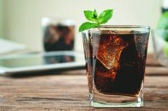 Exponeringsglas av cola som hälls till brättet Arkivbilder