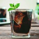 Exponeringsglas av cola som hälls till brättet Arkivbild
