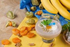 Exponeringsglas av den banansmoothien och physalisen Förnyande drinkar på en exotisk bakgrund Tropiska coctailar med frukter Royaltyfria Foton