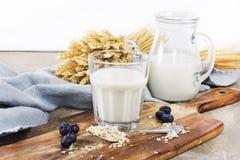Exponeringsglas av den ekologiska havren mjölkar med bär på träskrivbordet Arkivfoton