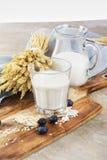 Exponeringsglas av den ekologiska havren mjölkar med bär på träskrivbordet Royaltyfri Foto