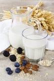 Exponeringsglas av den ekologiska havren mjölkar med bär på träskrivbordet Royaltyfri Fotografi