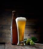 Exponeringsglas av den kalla skummande ölbruntflaskan av öl och flygtur på en mörk träbakgrund Arkivbilder