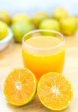 Exponeringsglas av den nya tangerin, orange fruktsaft med den skivade apelsinen på wo Arkivbilder