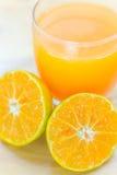 Exponeringsglas av den nya tangerin, orange fruktsaft med skivad orange halv nolla Arkivbild