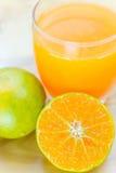 Exponeringsglas av den nya tangerin, orange fruktsaft med skivad orange halv nolla Royaltyfri Bild