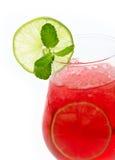 Exponeringsglas av den röda coctailen med limefruktskivor Arkivfoto