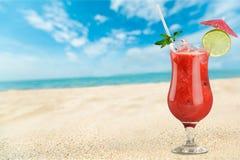 Exponeringsglas av den röda coctailen på stranden arkivfoton