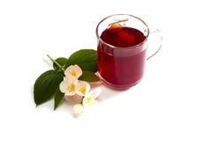 Exponeringsglas av det röda teet dekorerade med en blommafilial Fotografering för Bildbyråer