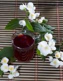 Exponeringsglas av det röda teet som dekoreras med blomman, förgrena sig Royaltyfri Bild