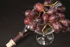 Exponeringsglas av druvor med vinflaskan Arkivfoto