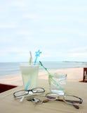Exponeringsglas av dryck och glasögon vid stranden royaltyfri foto