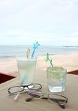 Exponeringsglas av dryck och glasögon vid stranden royaltyfria foton