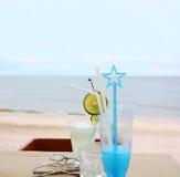 Exponeringsglas av drycken för två och glasögon vid stranden arkivbilder