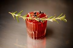 Exponeringsglas av en röd alkoholiserad coctail dekorerade med en kvist av bär för rosmarin och för den svarta vinbäret royaltyfri fotografi
