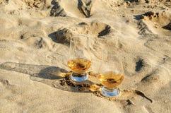Exponeringsglas av enkel malt för whisky på sandstranden, ett exponeringsglas av tasti Arkivbilder